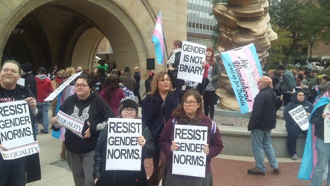 Protesters hold signs at Milwaukee City Hall Thursday to protest President Donald Trump's gender initiative.