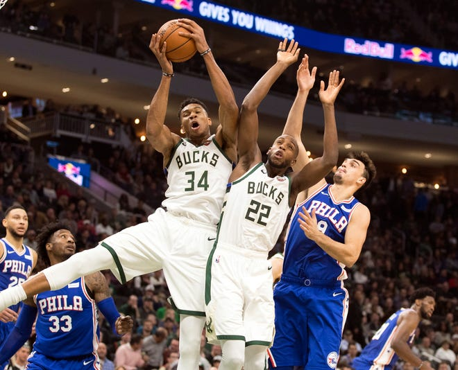 Giannis Antetokounmpo wins a rebound battle with teammate Khris Middleton and Dario Saric of the 76ers during the Bucks' 126-108 victory on Wednesday night.