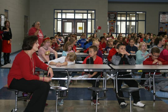 Hackler Intermediate School Principal Allyson Dewey sits with her students during Thursday morning's Red Ribbon Week Pep Rally. Ninth-grade students from Mountain Home Junior High's band and cheerleading squad performed, along with students in Vicki Banter's advisory group who performed anti-drug skits for the younger students.