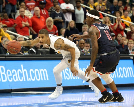 Auburn guard Samir Doughty (left), pictured playing for VCU, dribbles the ball Richmond guard De'Monte Buckingham (11) in overtime at the PPG Paints Arena on March 11, 2017, in Pittsburgh, PA.