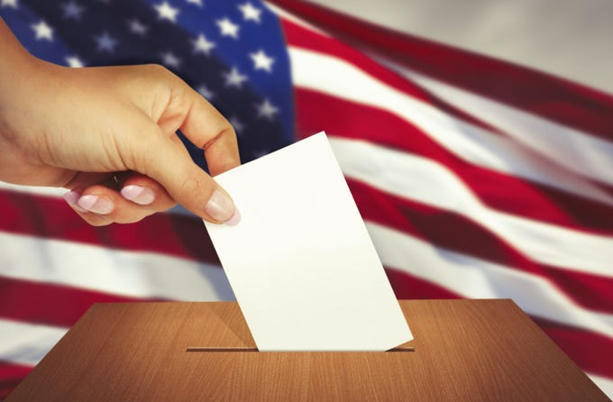 Hand putting a ballot into ballot box with american flag behind