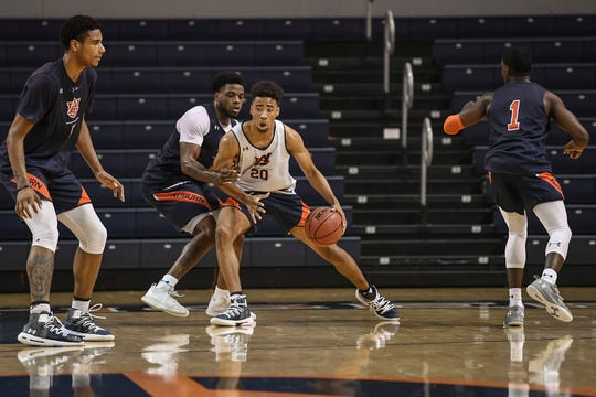 Auburn freshman Myles Parker (20) goes up against Malik Dunbar during practice.