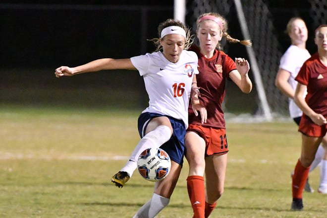 Oakland's Faith Adams (16) controls the ball while Ravenwood's Tori Case defends during Wednesday's AAA quarterfinal.