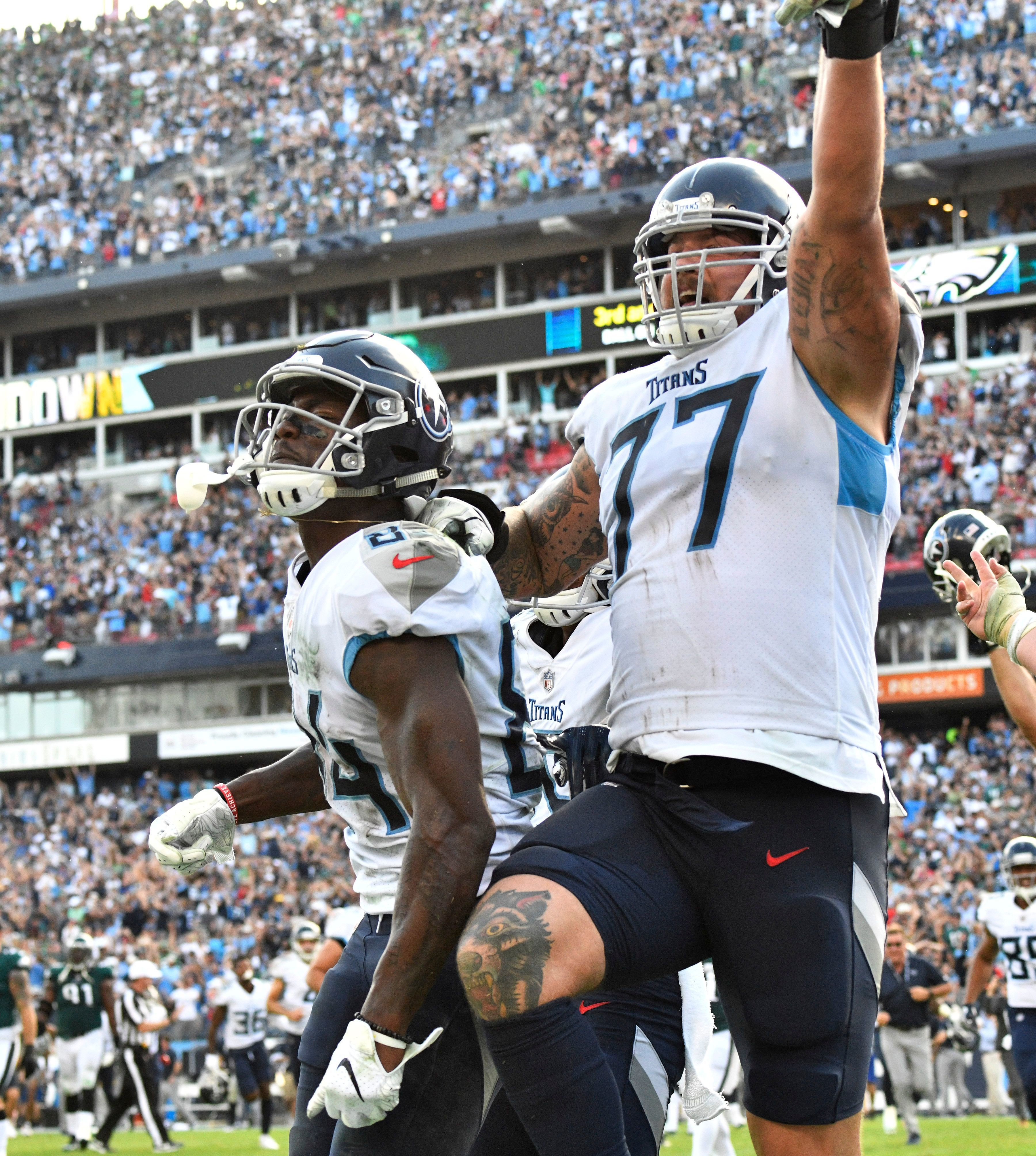 Titans offensive tackle Taylor Lewan (77) and wide receiver Corey Davis (84) celebrate the game-winning touchdown catch in overtime Sunday.