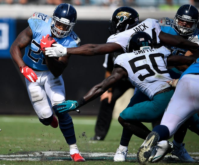 Titans running back Derrick Henry (22) tries to get past Jaguars defenders during the game in September at TIAA Bank Field.