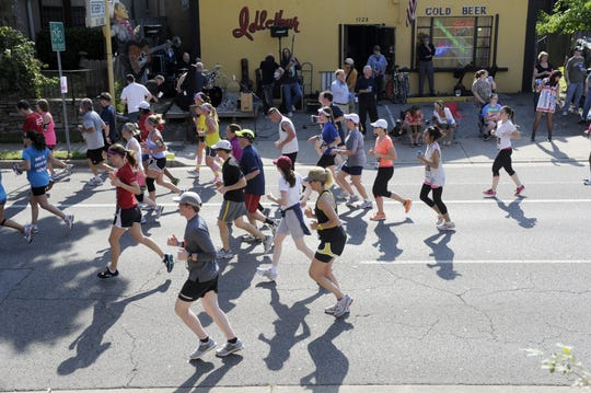 Country Music Marathon runners cast shadows as they run past Bobby's Idle Hour on April 28, 2012, on Music Row.