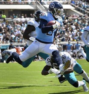 Titans quarterback Marcus Mariota (8) leaps over Jaguars cornerback A.J. Bouye (21) during the second quarter of their game Sept. 23.