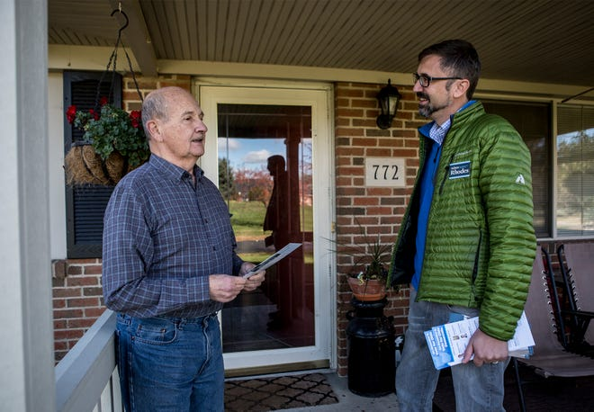 Adam Rhodes, who is running for county commissioner, speaks with Heath resident Jim Nemeth during a door-to-door campaign to remind residents to vote Nov. 6.