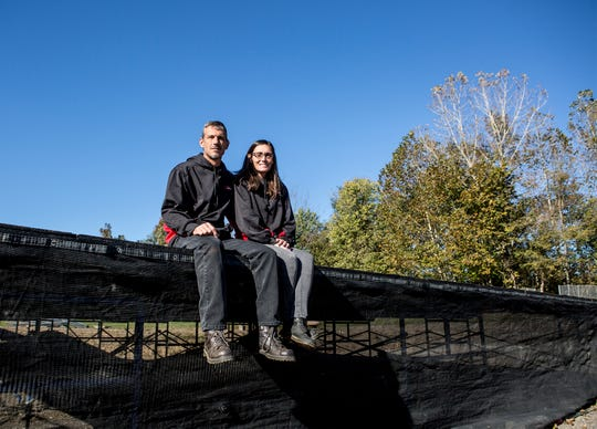 Devon White and Sheri Mertz sit on the stage they recently purchased to host local bands on their property on the south end of Newark. The couple want their venue Roost on the River, to be an affordable and family friendly option for concert goers.