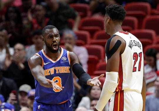 New York Knicks guard Tim Hardaway Jr. (3) argues a call as Miami Heat center Hassan Whiteside (21) looks on during the first half of an NBA basketball game, Wednesday, Oct. 24, 2018, in Miami.