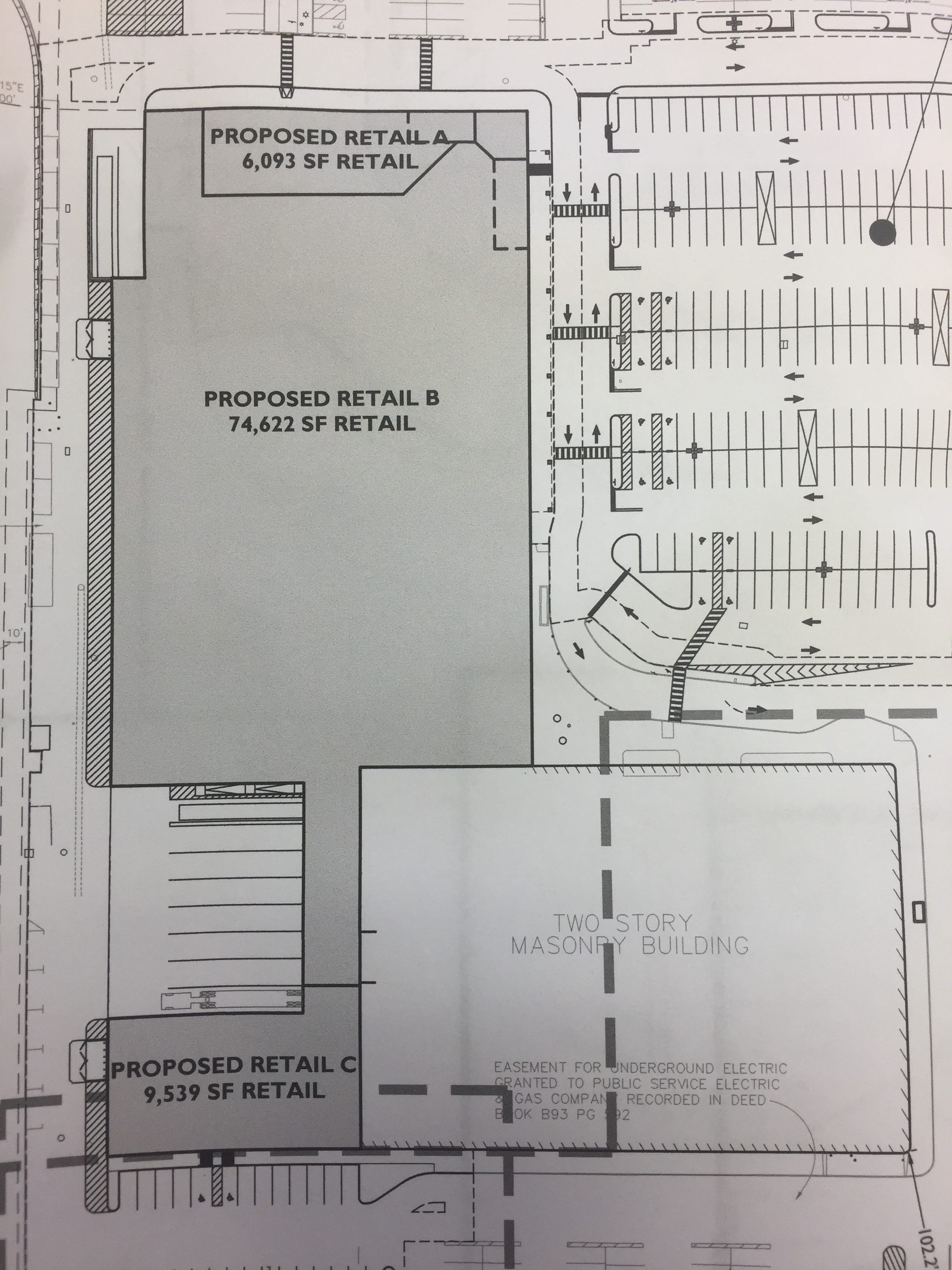 An engineer's drawing shows the dimensions of the future supermarket and adjacent retailers, all of which are shaded.
