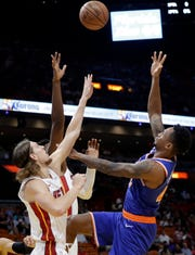 New York Knicks forward Lance Thomas, right, loses control of the ball as Miami Heat forward Kelly Olynyk, left, and center Hassan Whiteside, center, defend during the first half of an NBA basketball game, Wednesday, Oct. 24, 2018, in Miami.
