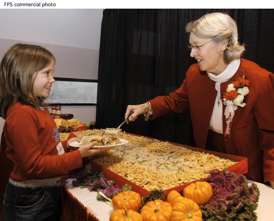 Dorcas Reilly, right, inventor of the Campbell's Soup Green Bean casserole serves a helping of the casserole to Dominique Cupp, 8, from Roosevelt Elementary School in Hubbard, OH, at the National Inventors Hall of Fame in Akron, OH, Tuesday, Nov. 19, 2002. The original recipe of the casserole was donated to the Hall of Fame archives by Reilly, former manager of Campbell's kitchens. The caserole has become a favorite during the holiday season alongside the turkey in over 20 million homes. (Feature PhotoService)