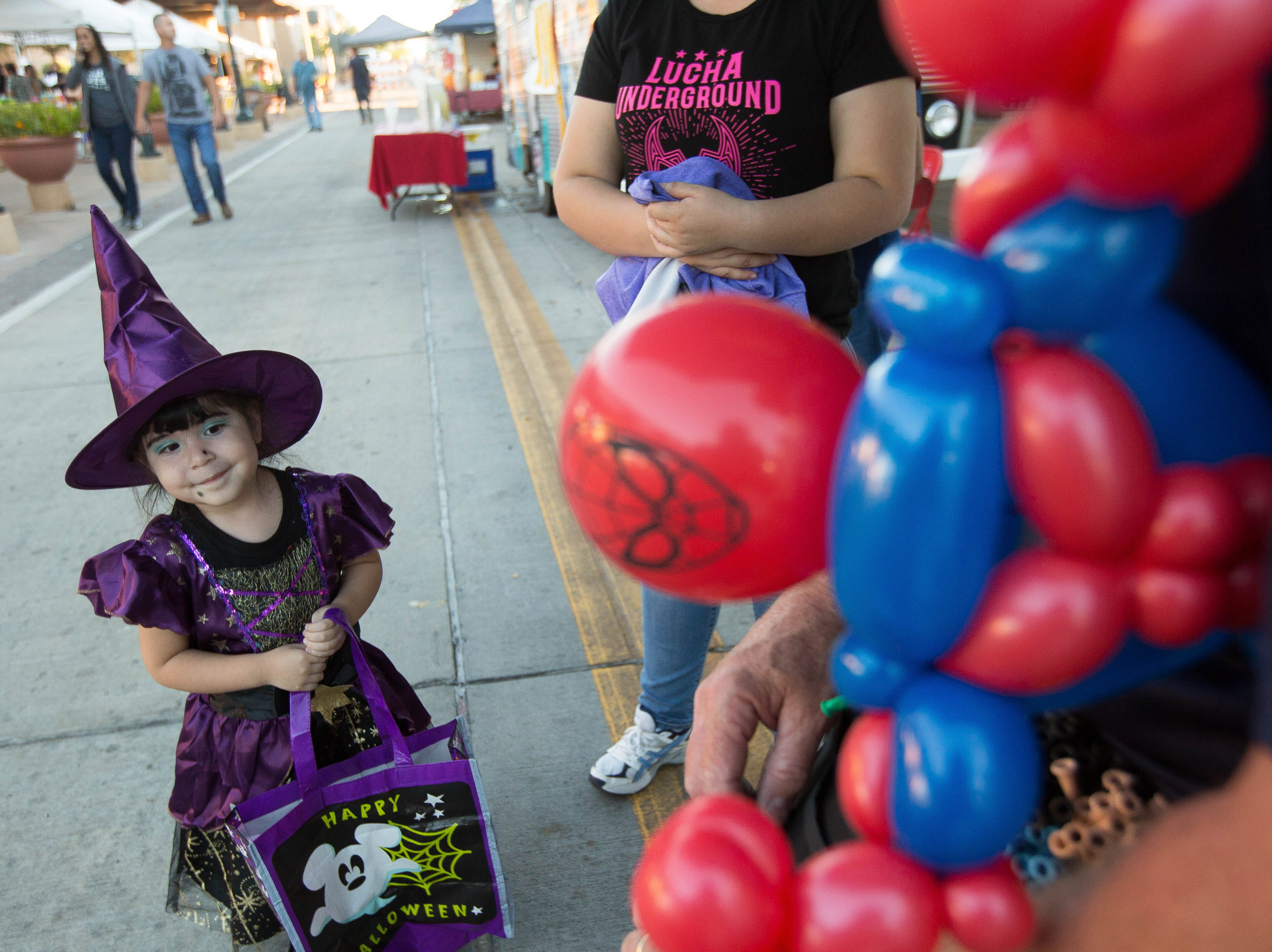 Bianca Tovar, 3, looks on as Matt Hall, with Party Animals Balloons and more, makes her a Spiderman balloon figure, Wednesday, October 24, 2018 at the Plaza de Las Cruces during the Farmers Market Fall Festival.
