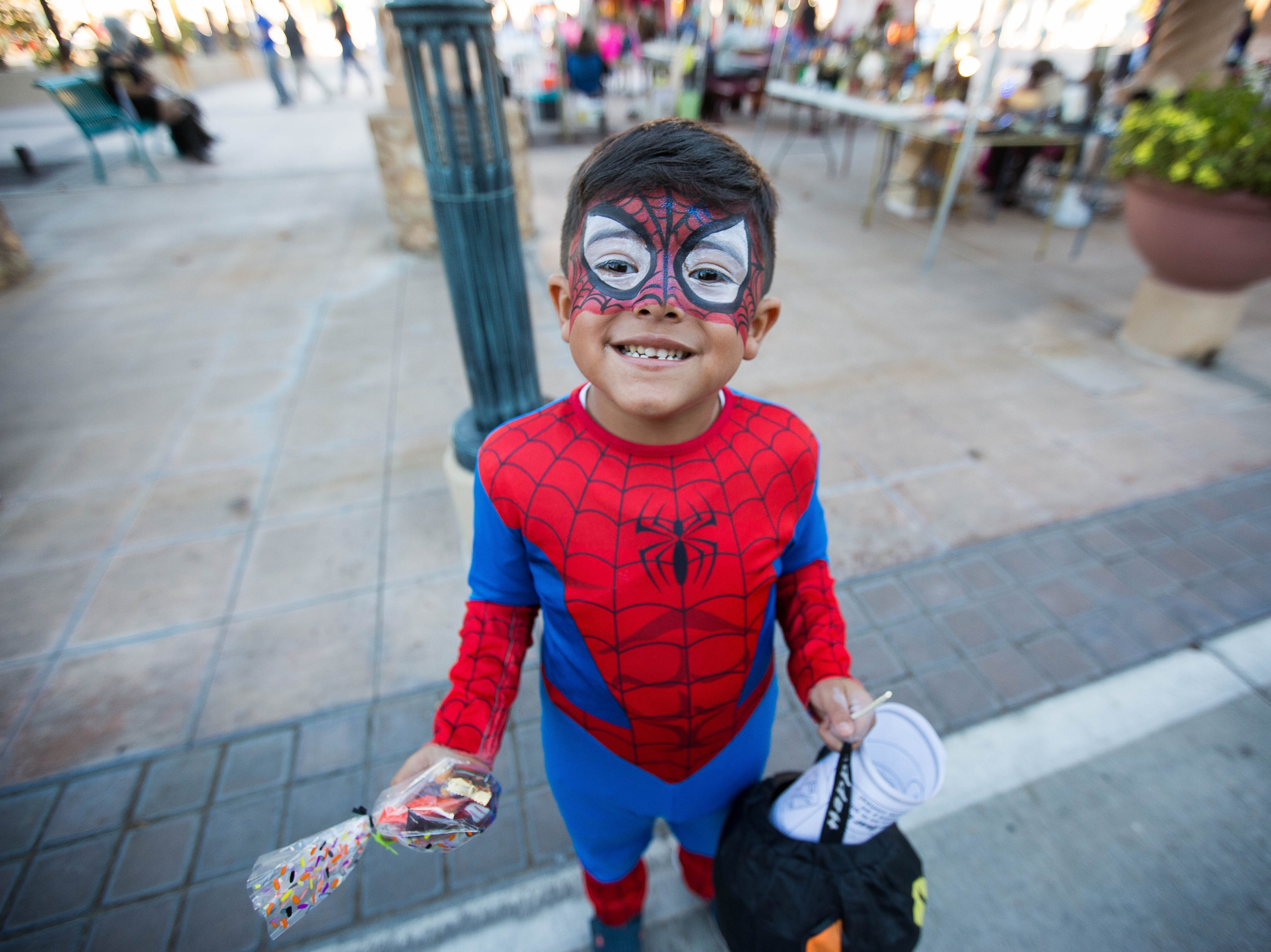Jayden Zamora, 4, dressed in a Spiderman costume waits to get his balloon Spiderman figure fixed by Matt Hall of Party Animals Balloons and More, during the Farmers Market Fall Festival at the Plaza de Las Cruces, Wednesday October 24, 2018.