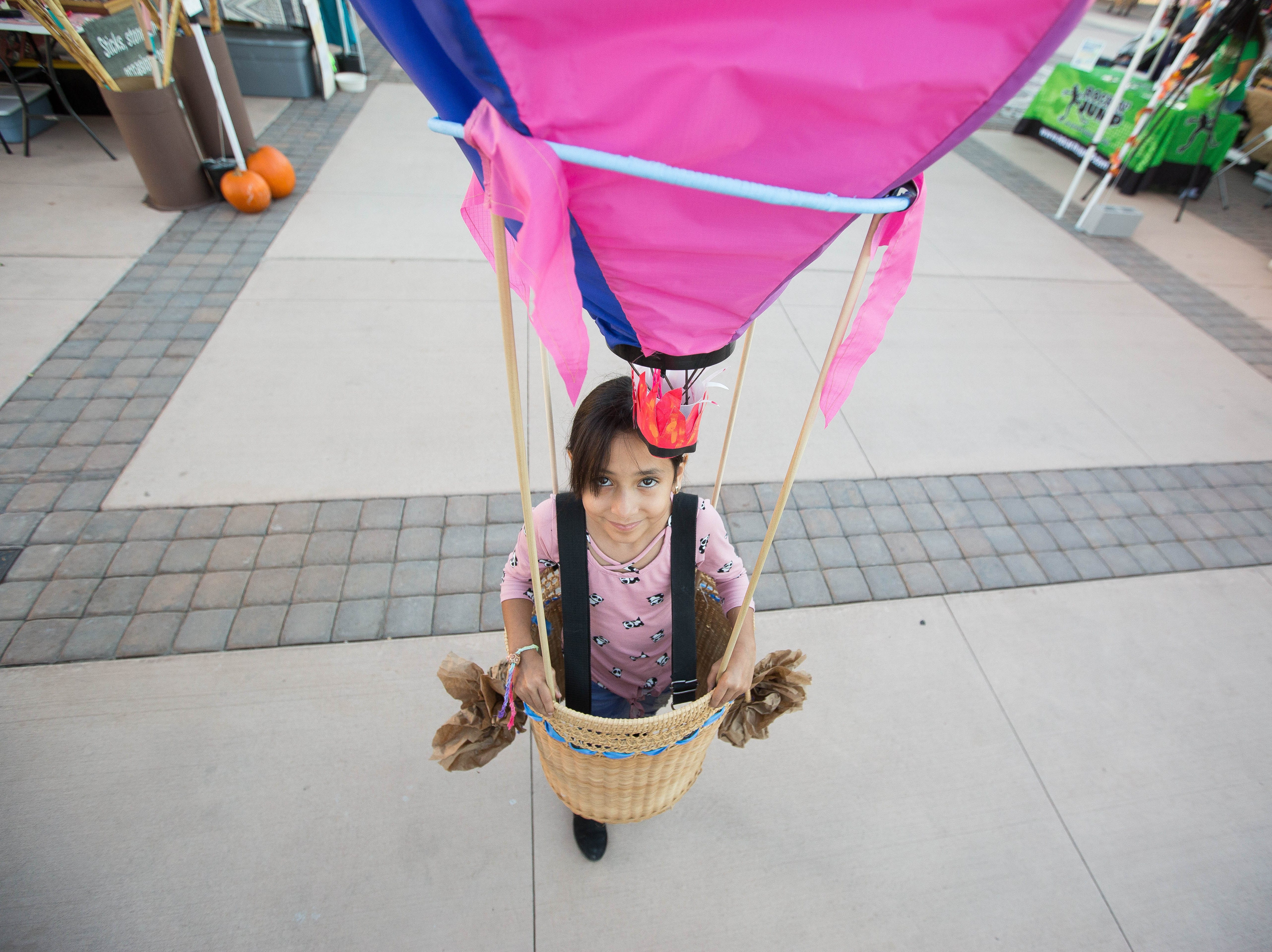 Sarah Vau, 9, dressed in a hot air balloon costume walking through the plaza de Las Cruces, Wednesday October 24, 2018 during the Farmers Market Fall Festival. Vau won first place in the costume contest, which is one of the many activities held at the event, from a mummy wrap to pumpkin painting.