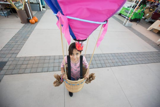 Sarah Vau, 9, dressed in a hot air balloon costume, walks through the plaza de Las Cruces, Wednesday October 24, 2018 during the Farmers Market Fall Festival. Vau won first place in the costume contest, which was one of the many activities held at the event, from a mummy wrap to pumpkin painting.