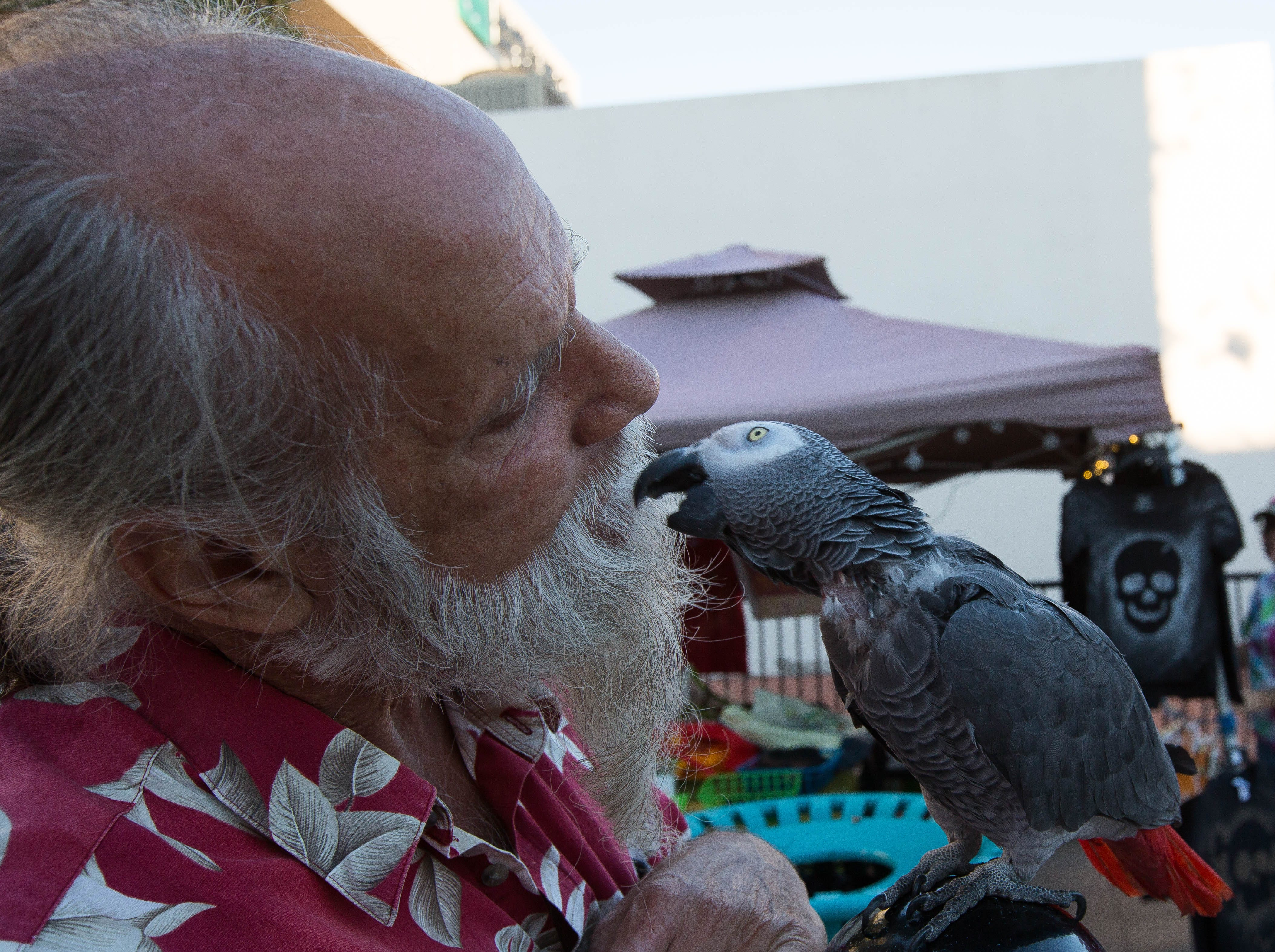 Chris Van Inga, gives a kiss to his parrot Phinneas, during the Farmers Market Fall Festival, Wednesday October 24, 2018.