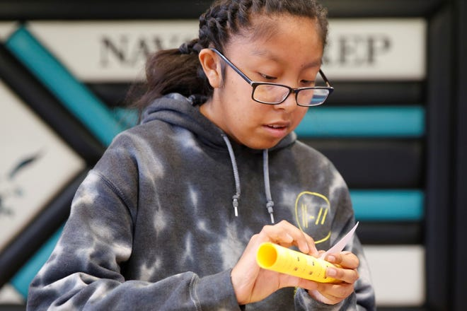 Navajo Preparatory School sophomore Kamorie Thomas pieces together card stock paper as part of a stomp rocket activity at the STEM Exploration Day on Thursday at Navajo Prep in Farmington.