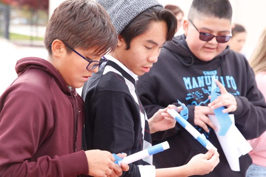 Chief Manuelito Middle School eighth-graders Kaden Bitsie, left, Rynil Lachica and Eli Joe use paper and tape to build rockets during the STEM Exploration Day on Thursday at Navajo Preparatory School in Farmington.