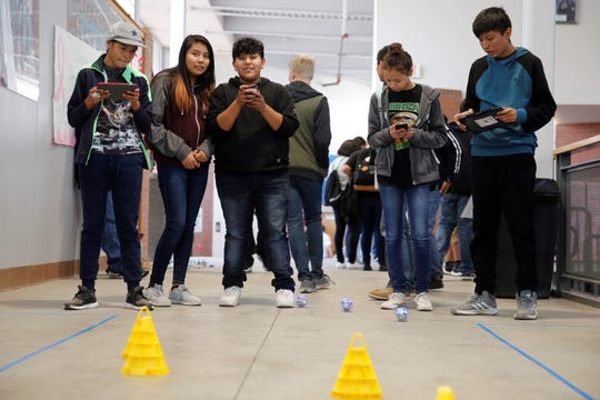 From left, Gallup High School students Orion Lomaintewa, Destiny Slinkey and Robyn Sandoval and Thoreau High School students Taylor Long and Elias Woody learned how to program the movement of Sphero robots at the STEM Exploration Day on Thursday at Navajo Preparatory School in Farmington.