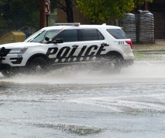 police car drives through riverlet