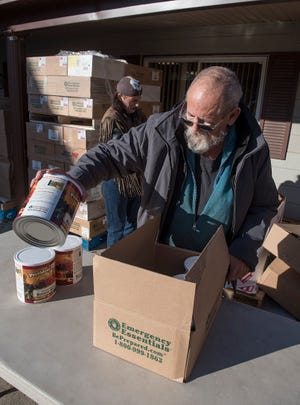 A veteran who is known only as Skinner unloads boxes of food for distribution.