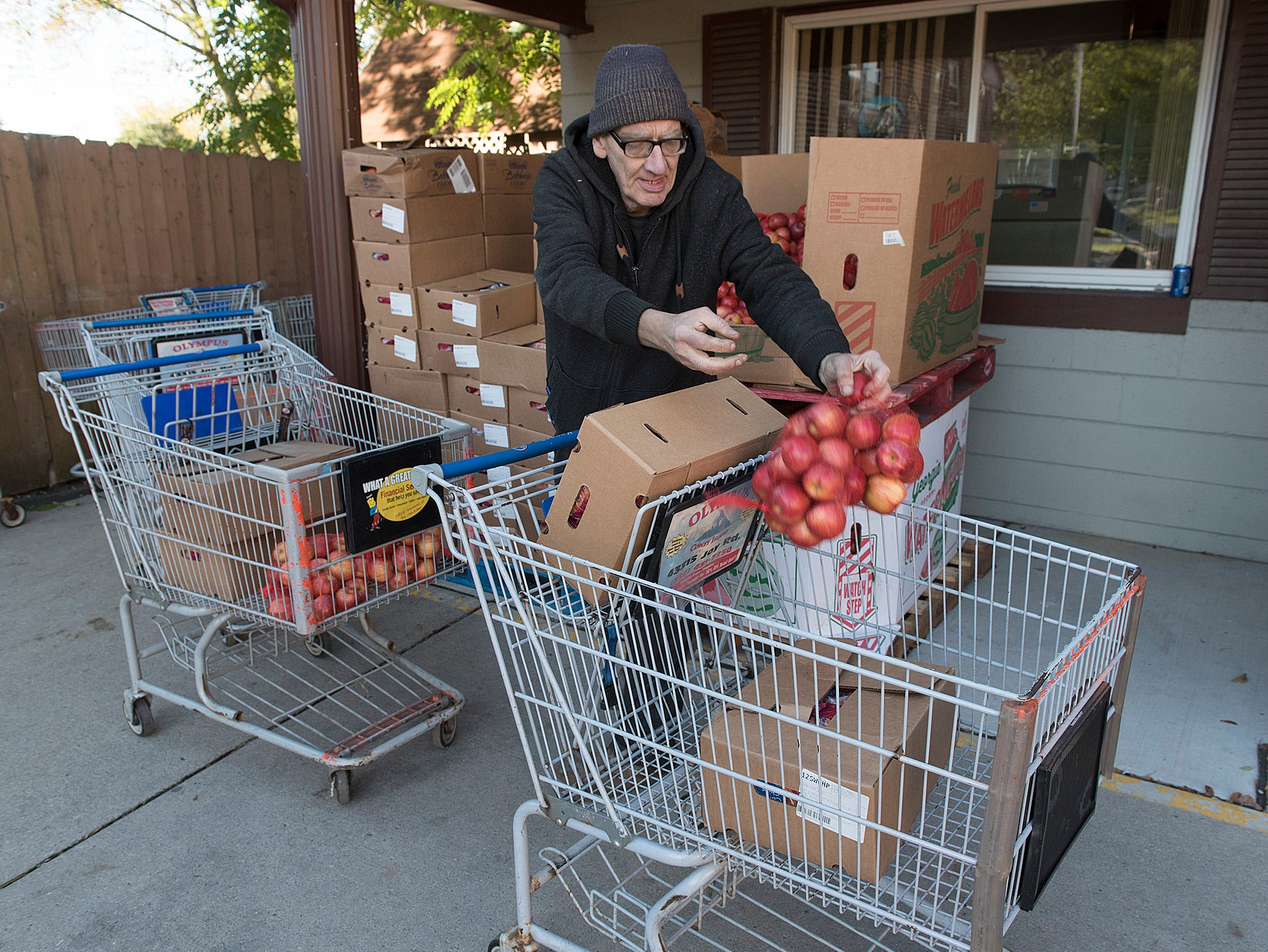 Jacques Pavlik loads carts with food for needy veterans.