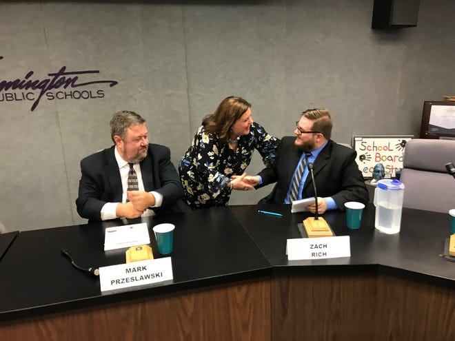 Pamela Green shakes hands with fellow school board candidates Zach Rich (right) and Mark Przeslawski following Tuesday's candidate forum.