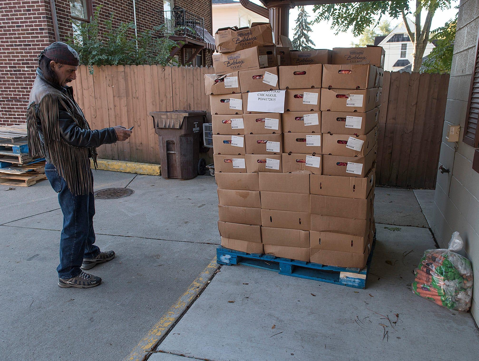 Nick Dunsky counts cartons of food ready for distribution.