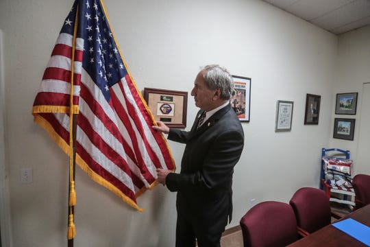 Republican Senator Jeff Stone, Pharm.D. Twenty-Eighth Senate District of the California Legislature adjusts a flag in his office in Indio on Thursday, October 25, 2018.