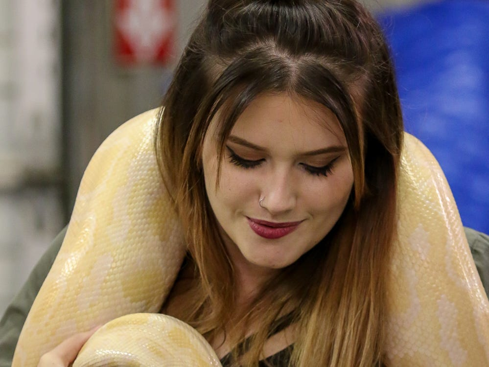 Ashley Fowler, 18, of Milton, holds a Burmese python from Pensacola-based Reno's Reptiles during the 84th annual Pensacola Interstate Fair on Monday, October 22, 2018.