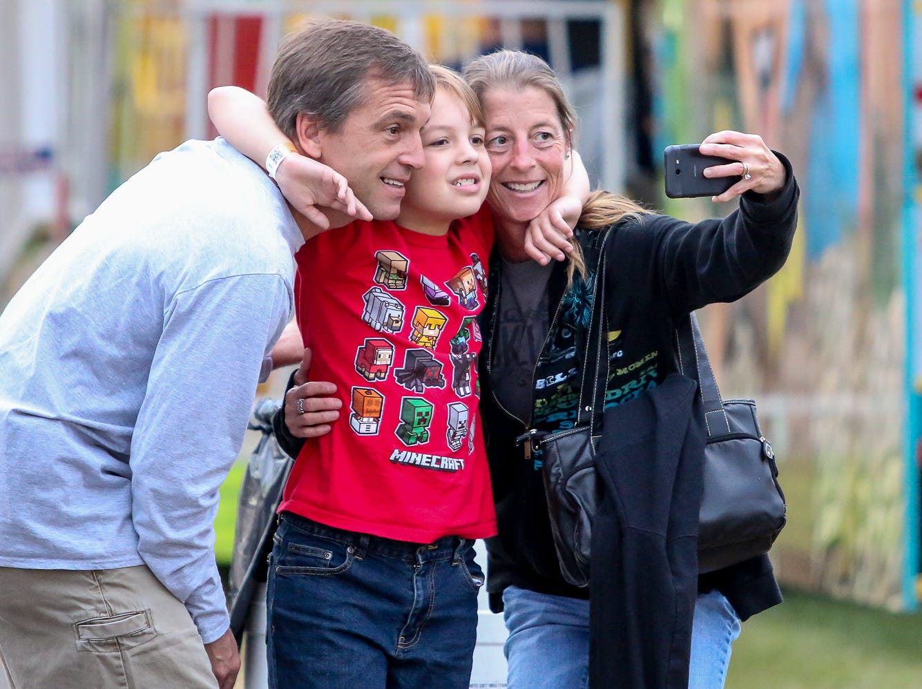 The Cunningham family, Darrin, left, Jake, and Ashley, take a quick picture during the 84th annual Pensacola Interstate Fair on Monday, October 22, 2018.