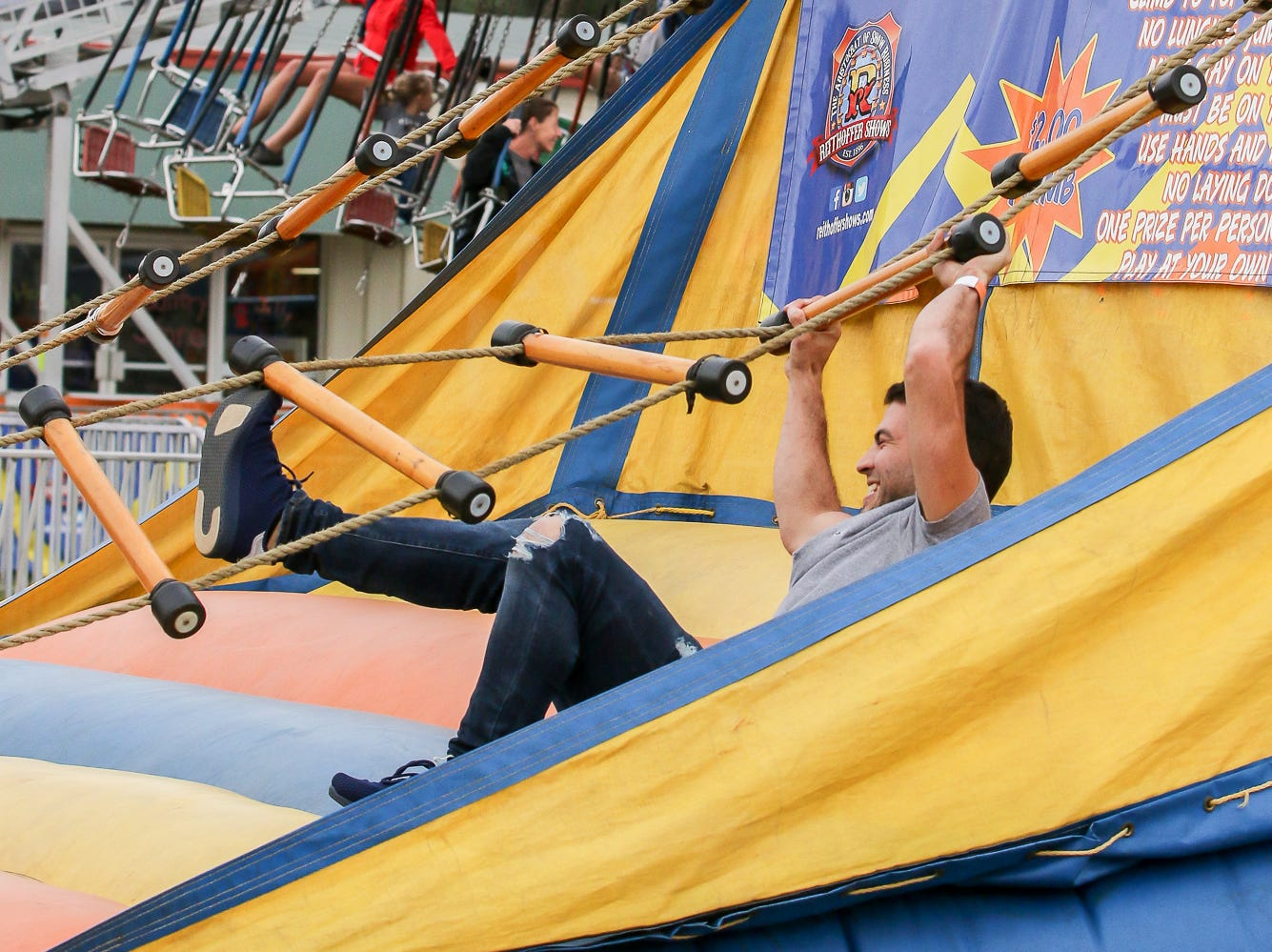 Camilo Norena, of Panama City, tries his hand at the rope ladder game during the 84th annual Pensacola Interstate Fair on Monday, October 22, 2018.