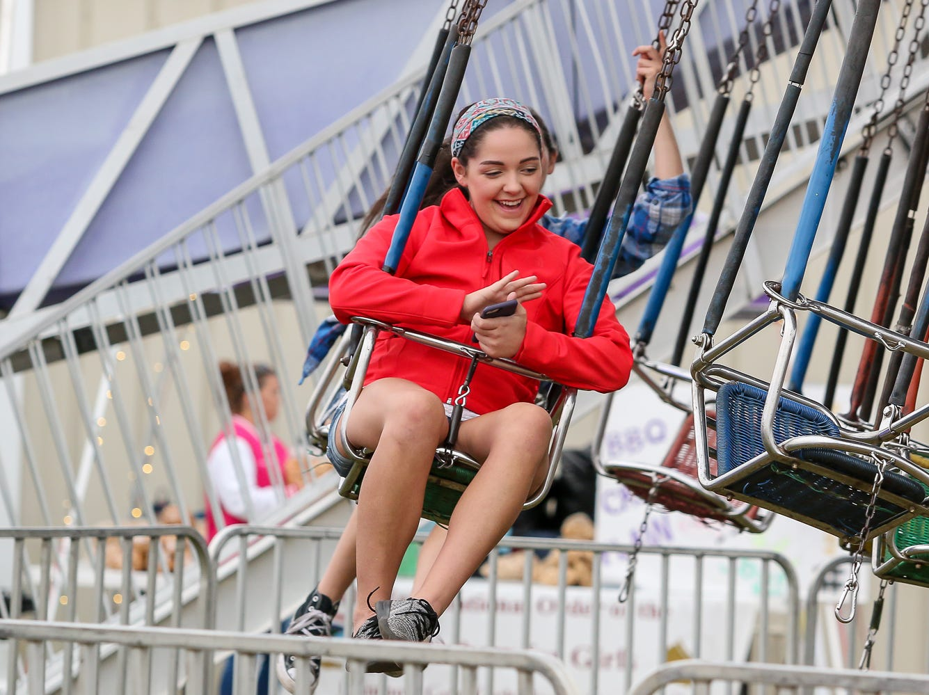 Chloe Whitfield, 24, of Molino, smiles as she rides some swings during the 84th annual Pensacola Interstate Fair on Monday, October 22, 2018.