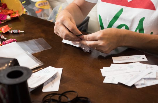 Michelle Salzman, the immediate past president of the Escambia County Council of PTAs, finishes making more than 1,000 candy bags on Thursday as part of an effort to encourage people to vote for a local referendum that would make the superintendent an appointed position.
