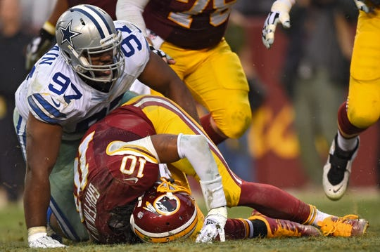 LANDOVER, MD - DECEMBER 28: Quarterback Robert Griffin III #10 of the Washington Redskins fumbles the ball as he is sacked by defensive tackle Terrell McClain #97 of the Dallas Cowboys in the fourth quarter at FedExField on December 28, 2014 in Landover, Maryland. The Dallas Cowboys won, 44-17. (Photo by Patrick Smith/Getty Images)