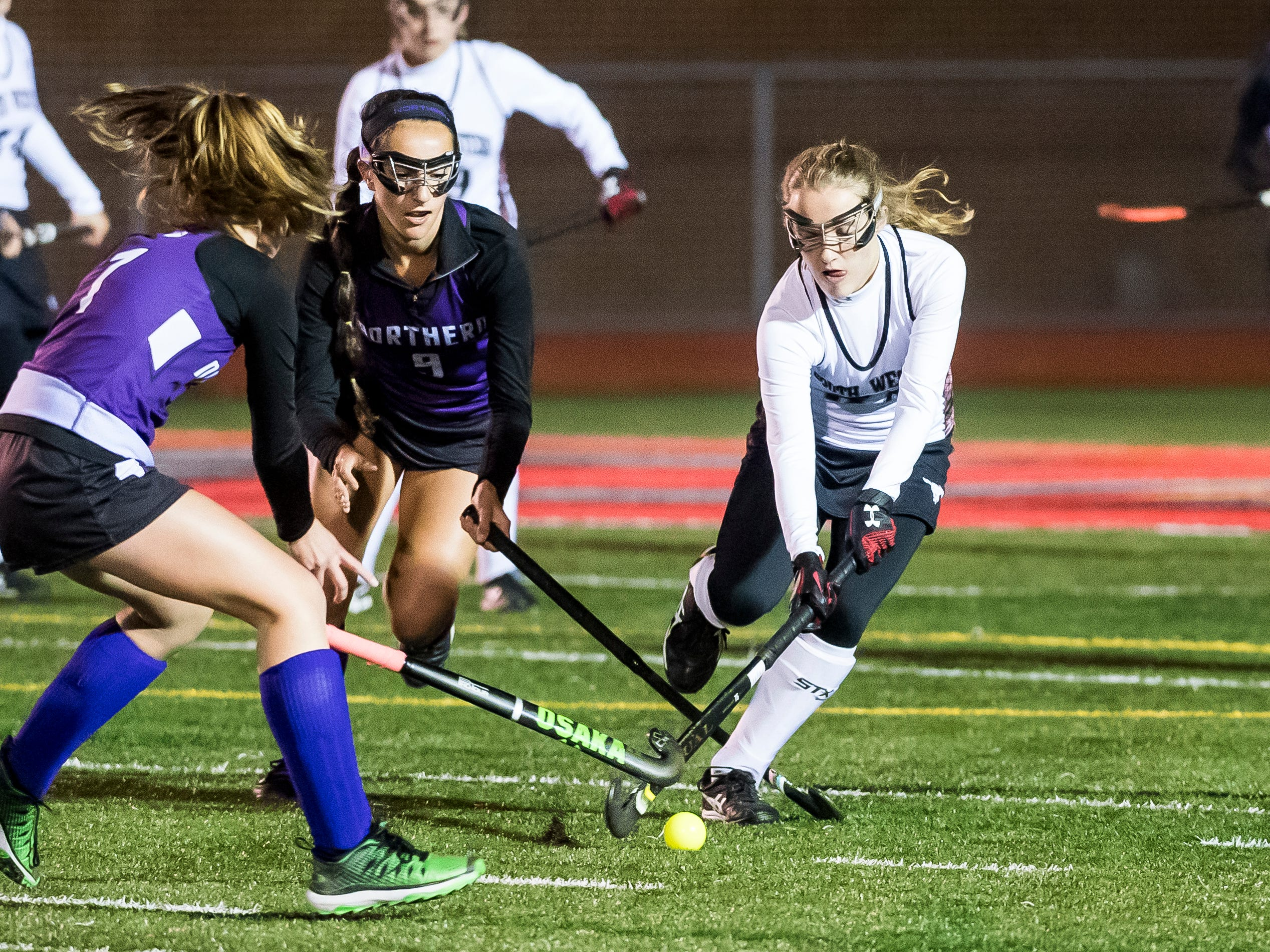 South Western Sophia Stranick battles for the ball with two Northern York players during a PIAA District III first round game at Bermudian Springs High School on Wednesday, October 24, 2018. The Mustangs fell 4-2.