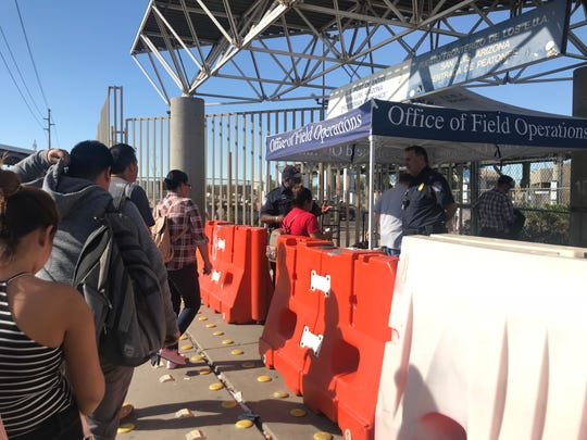 U.S. Customs officers set up a tent at the entrance of the San Luis pedestrian crossing to control the flow of people on Oct. 24, 2018. Pedestrians are asked to show their passports or visas. Migrants seeking asylum must wait until they are called to be processed.