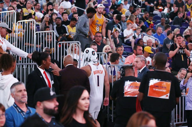 Devin Booker walks off the court after suffering a strained left hamstring during the Suns' 131-113 loss to the Lakers on Oct. 24 at Talking Stick Resort Arena.