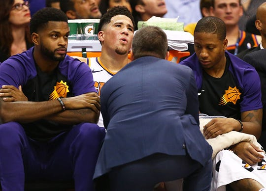 Devin Booker reacts as he's examined by a trainer after straining his left hamstring during the third quarter of a game against the Lakers.