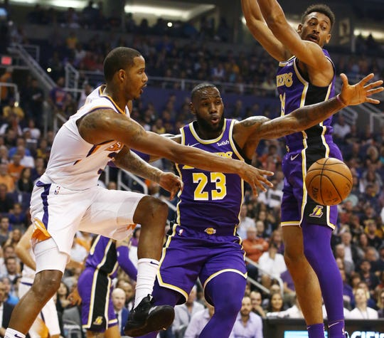 Trevor Ariza passes the ball under the hoop with pressure from LeBron James during the first half of the Suns' loss to the Lakers 131-113.