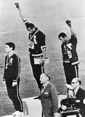 Tommie Smith (center) and John Carlos (right) raise their fists in the 1968 Olympic Games in Mexico City.