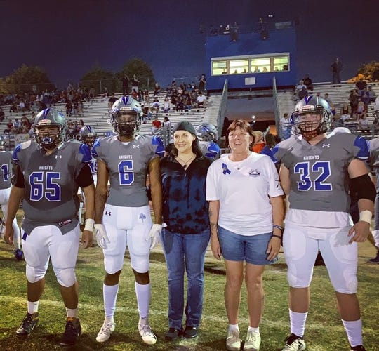 Westview players standing  with Love Notes founder Natalie Reilly (wearing jeans) and Debbie Edenhofer, who is the mother of the later trooper Tyler Edenhofer.