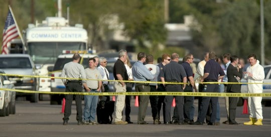 Law enforcement meet on the Main Street in front of a building where a packaged exploded Feb. 26, 2004. The director of Scottsdale's Office of Diversity & Dialogue and two other co-workers were injured when a package addressed to him exploded.