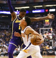 Devin Booker is defended by Kentavious Caldwell-Pope of the Lakers during the first half of a game at Talking Stick Resort Arena.