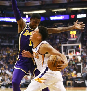 Devin Booker is pressured Kentavious Caldwell-Pope of the Lakers during the first half of a game Oct. 24 at Talking Stick Resort Arena.