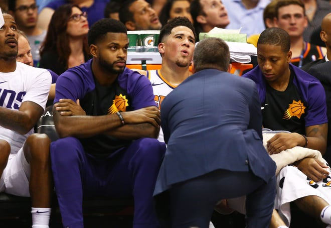 Devin Booker reacts as his leg is examined by a trainer during a game against the Lakers at Talking Stick Resort Arena.
