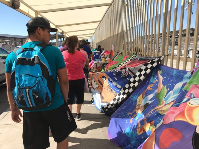 Passers-by look at the makeshift tents migrant families have set up outside the San Luis border crossing on Oct. 24, 2018. For months, hundreds of migrants have camped out here, waiting for their chance to legally claim asylum in the United States.