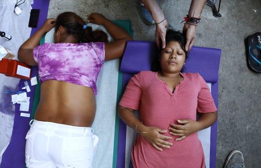 Dos mujeres centroamericanas reciben acupuntura y masaje por parte del grupo voluntario Ángeles de la Frontera, en Tijuana.